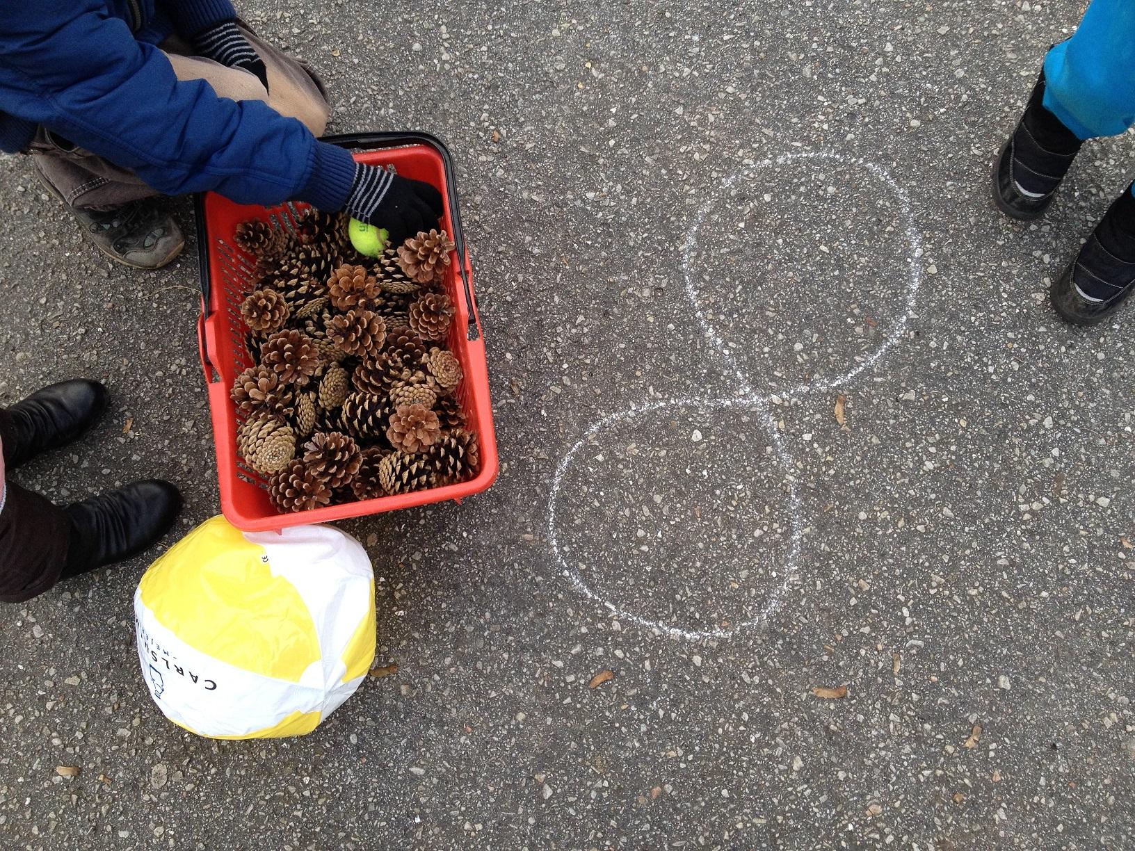 Bilden föreställer tre barn som ska lägga upp kottar i en ritad åtta.